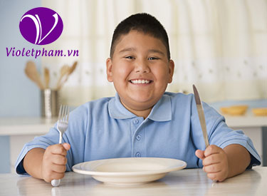 Hispanic boy holding silverware at table